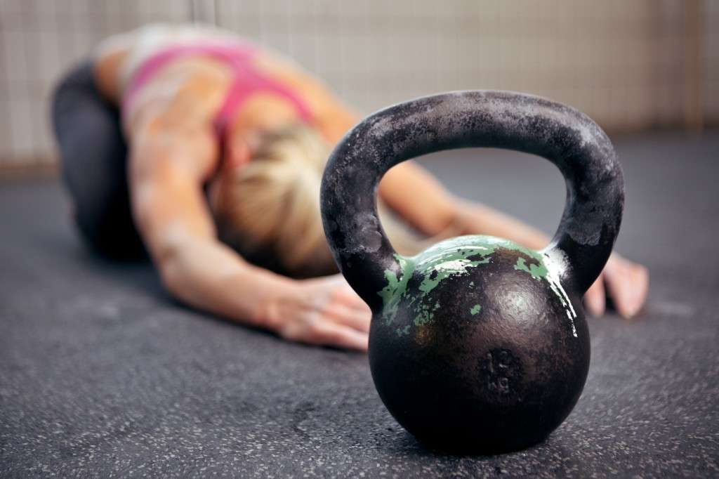 Young woman stretching her back after a heavy kettlebell workout in a gym