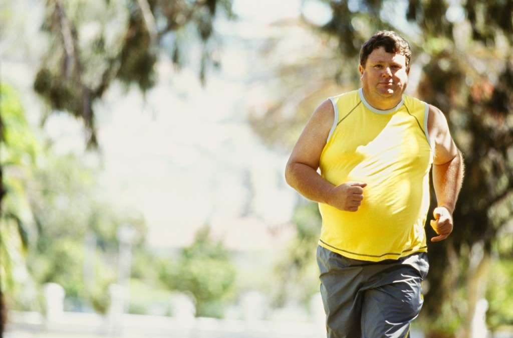 portrait of a mid adult man jogging in a park --- Image by © Royalty-Free/Corbis