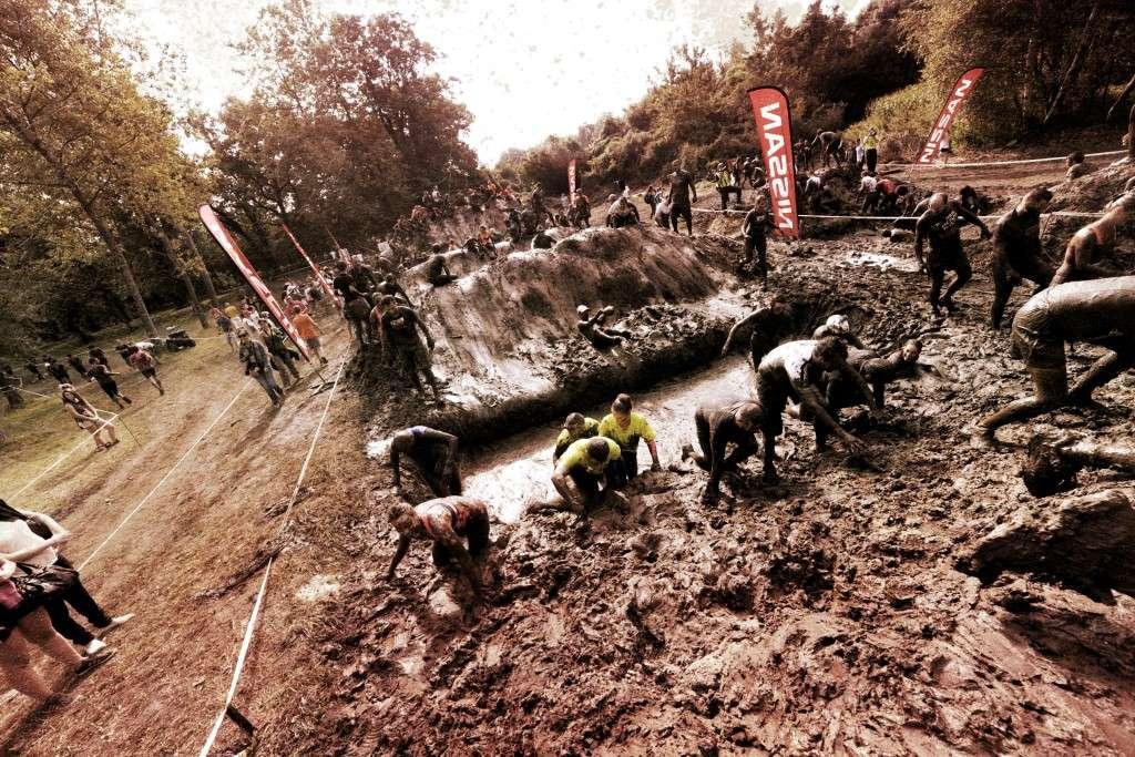 Photo Pierre Alessandri / ASO - Lac de Vénérieu - 07/09/2014 - The Mud Day Lyon 2014 - Libre de droits - Des Mud Guys franchissant l'obstacle CROSS OVER MUD MOUNTAINS