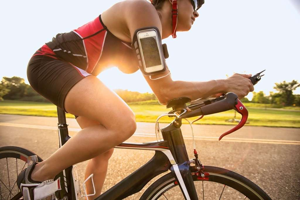 Portrait of cyclist listening music on smart phone while riding a road bike