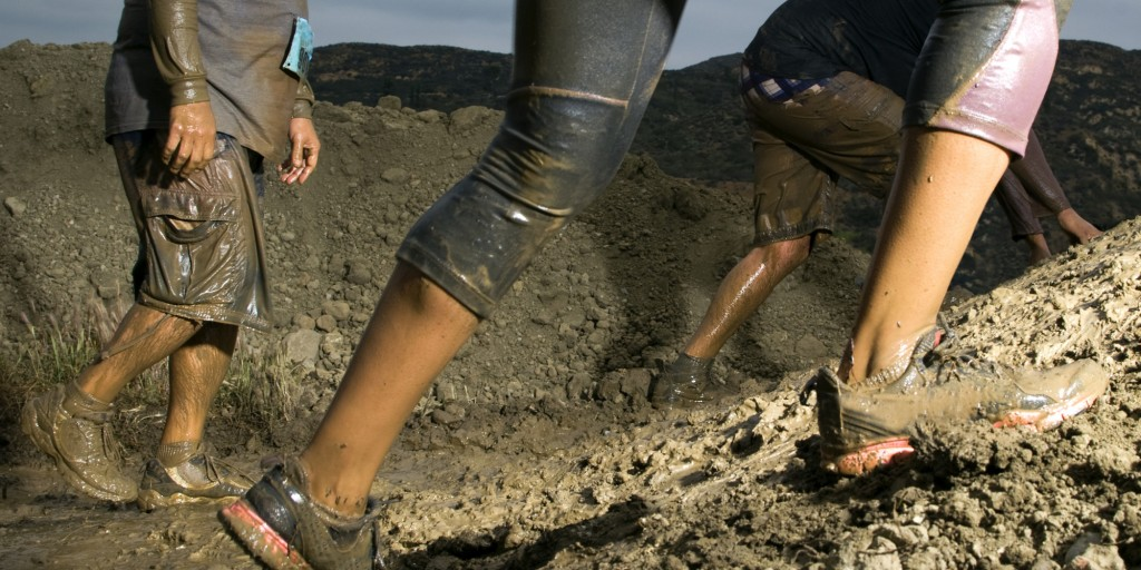 Legs and feet climbing up mud obstacle.